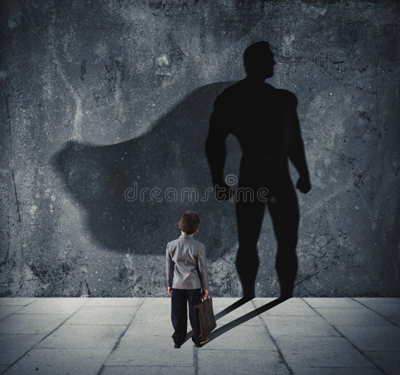 与他的特级英雄的阴影的年轻商人在墙壁上的 强有力的小人的概念 图库摄影