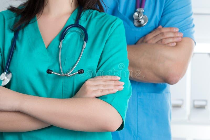 与他们的胳膊的两位医生standind在胸口横渡了 库存图片