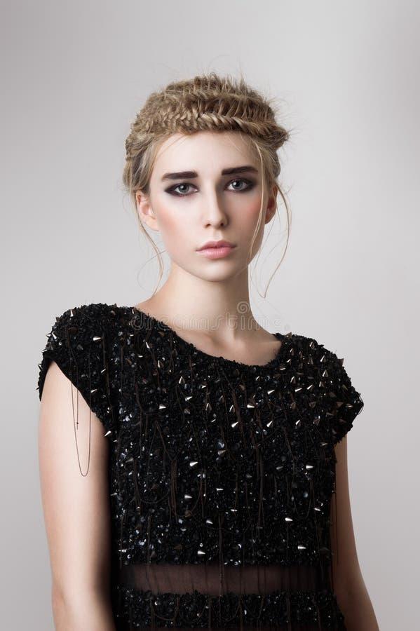 与黑礼服的时尚白肤金发的模型 库存照片
