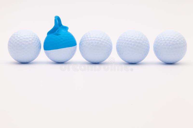 与滑稽的盖帽的白色高尔夫球在白色背景 免版税库存照片