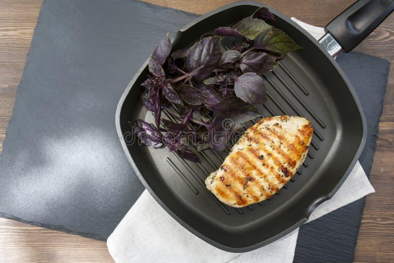 与紫罗兰色蓬蒿的烤鸡胸脯牛排在聚四氟乙烯平底锅gri 免版税库存图片