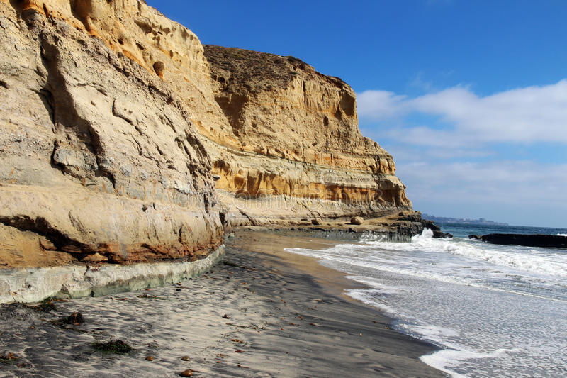 与黄色冲海滩的砂岩峭壁和波浪的和平的海岸线 免版税库存图片