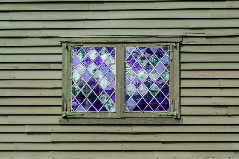 与紫色单块玻璃的双重窗口在殖民地大厦的墙壁的金刚石样式 图库摄影