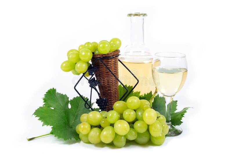 与绿色叶子、酒杯杯和酒瓶的新鲜的白葡萄充满在白色隔绝的白葡萄酒 图库摄影