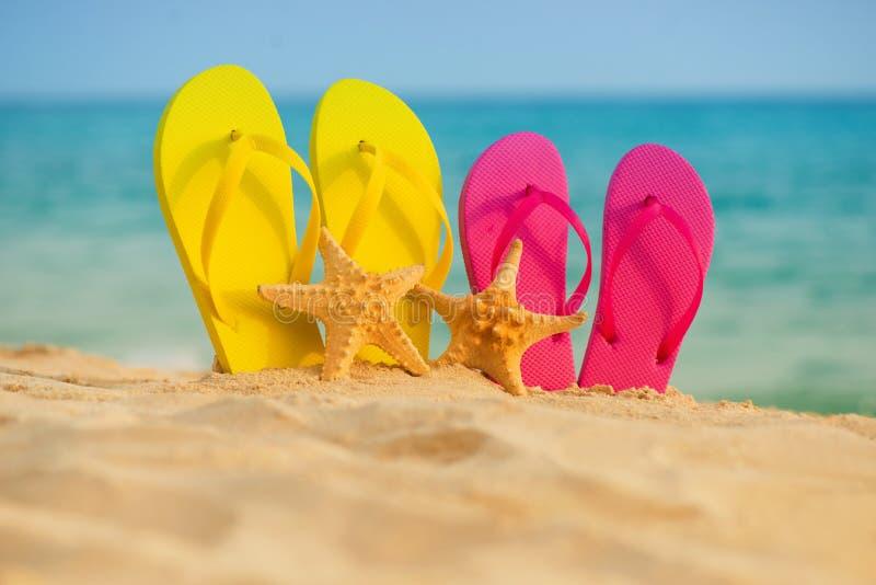 与黄色和桃红色凉鞋的海星在沙子站立以海为背景 图库摄影