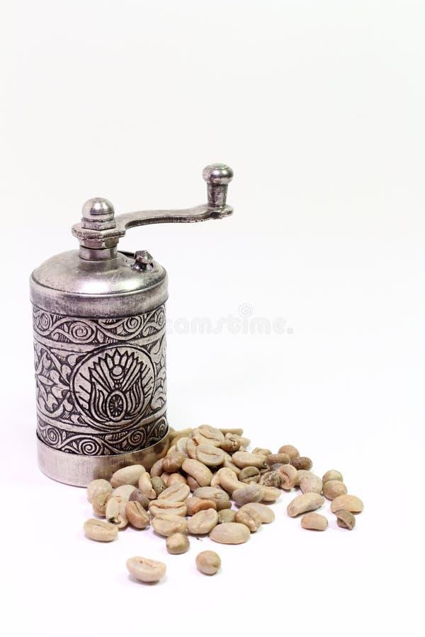 与绿色咖啡五谷的阿拉伯东方咖啡碾在白色背景的 免版税库存照片