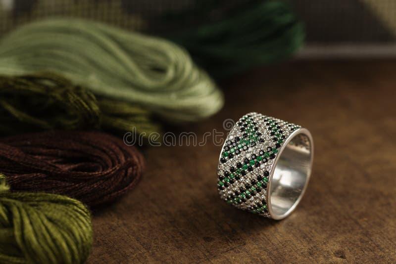 与绿色宝石的银色圆环 图库摄影