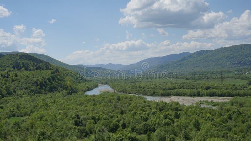 与绿色山森林和蓝色河的惊人的风景前面的 喀尔巴阡山脉的山顶视图 免版税图库摄影
