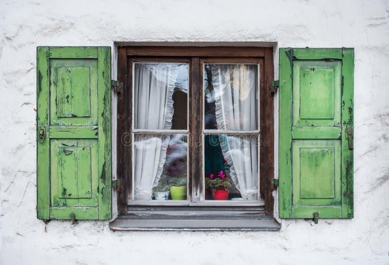 与绿色木shuttters的地道窗口在一个小镇  免版税库存照片