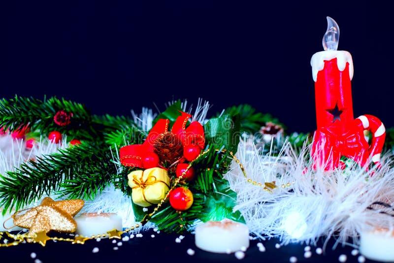 与绿色杉木,在黑背景的红色蜡烛的圣诞节装饰 库存照片