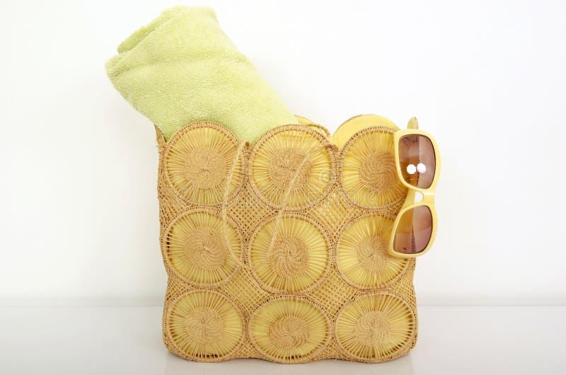 与绿色海滩毛巾和太阳镜的夏天柳条袋子 免版税库存照片