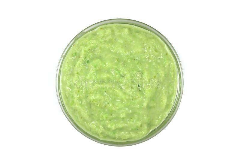 与绿色的被磨碎的辣根酱在玻璃容器 库存图片