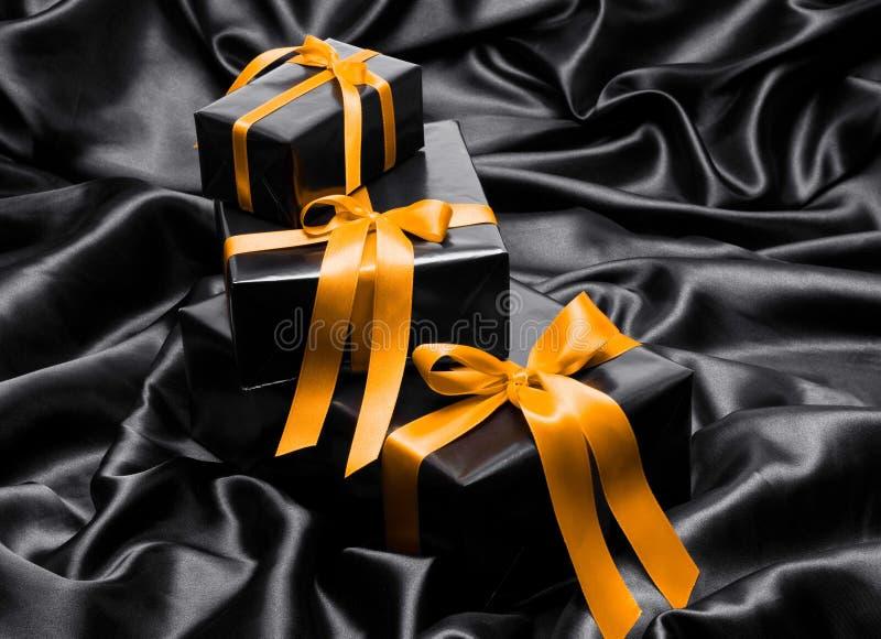 与黄色缎丝带的黑礼物boxe 库存图片