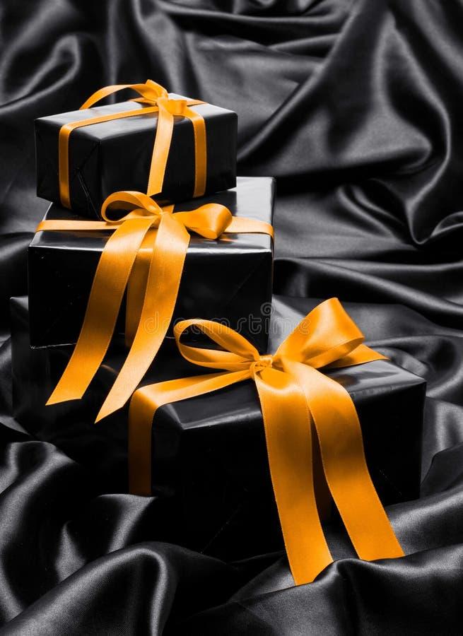 与黄色缎丝带的黑礼物boxe 免版税库存图片