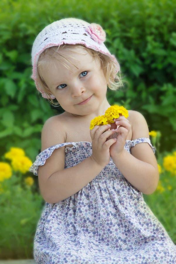 与花的卖弄风情的小女孩画象 免版税库存照片