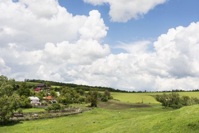 与绿色领域和小村庄的风景 免版税库存图片