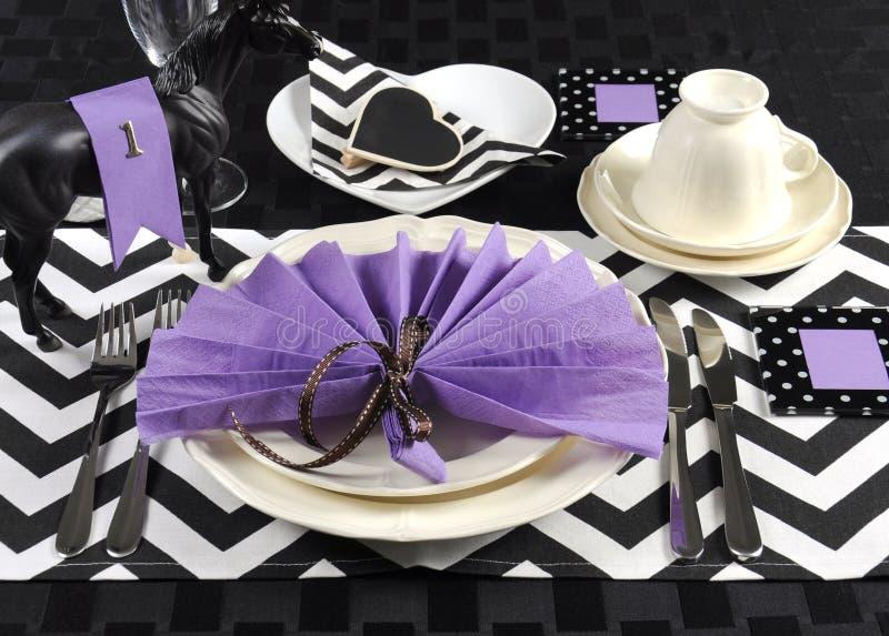 与紫色题材党午餐桌的黑白V形臂章 免版税库存照片