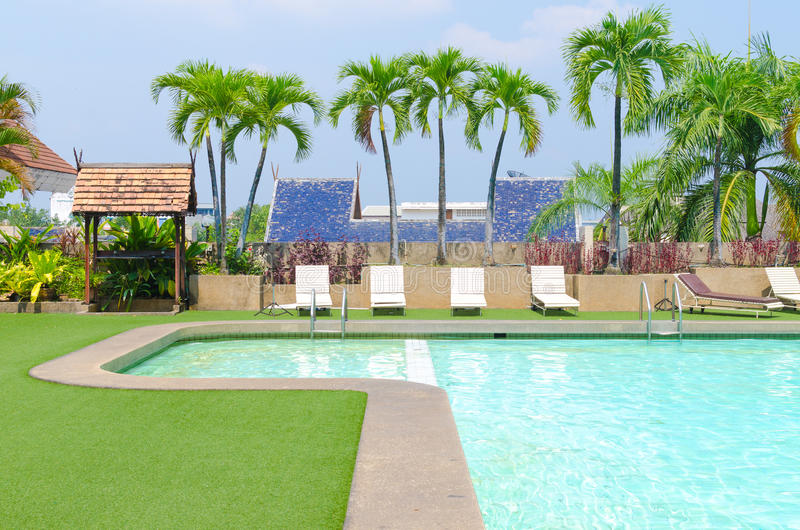 与绿草和棕榈的游泳池在旅馆关闭 库存照片