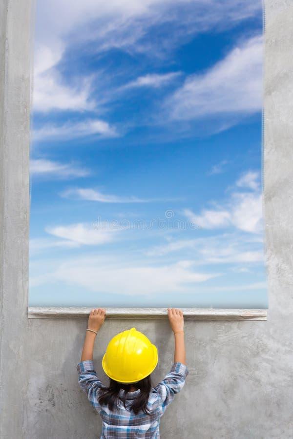 与绘蓝天的小女孩工程学在墙壁背景 库存照片