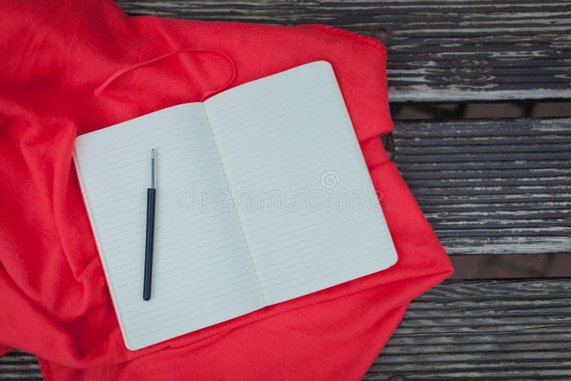 与说谎在一条红色毯子的一支黑笔的空白的笔记薄 背景黑暗木 库存图片