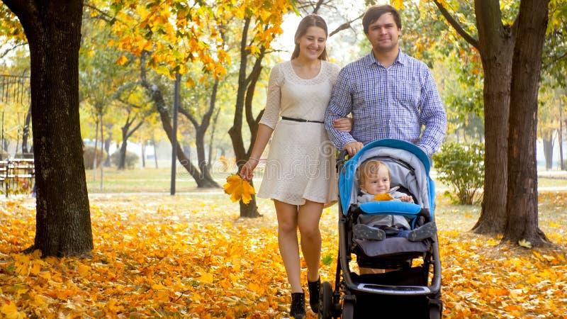 与1走在美丽的秋天公园的岁男婴的愉快的年轻家庭 库存照片