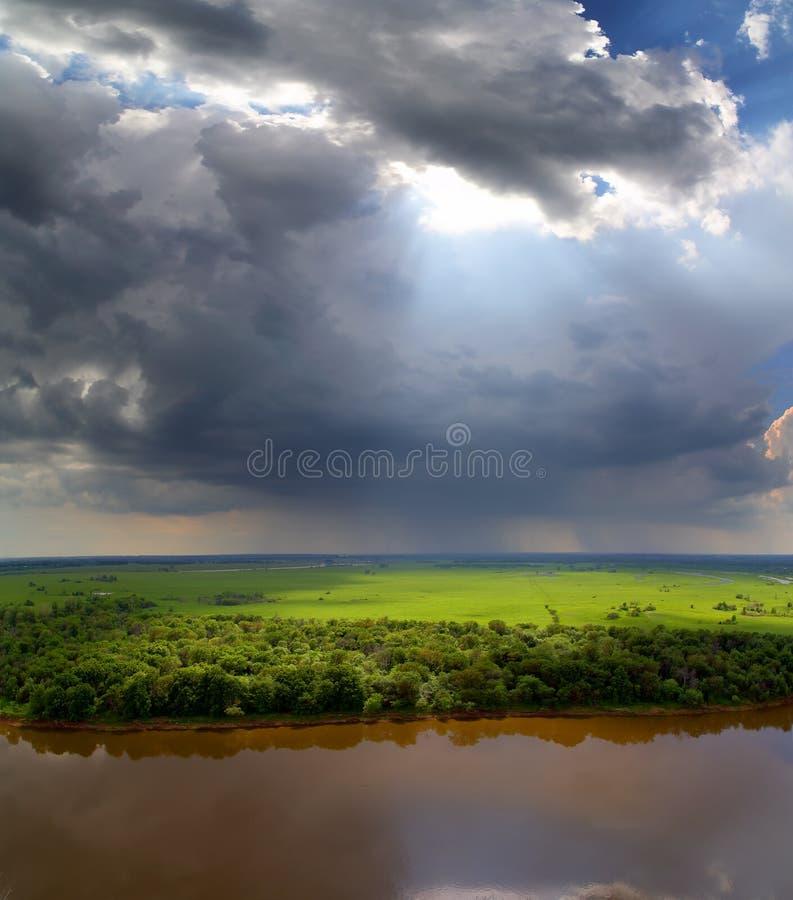 与暴风云和河的风景 库存照片