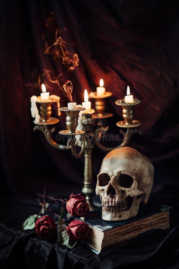 与头骨、书和烛台的静物画 图库摄影