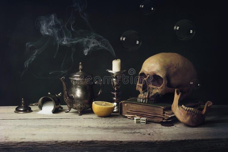 与头骨和茶具的Vanitas,书和肥皂泡 图库摄影