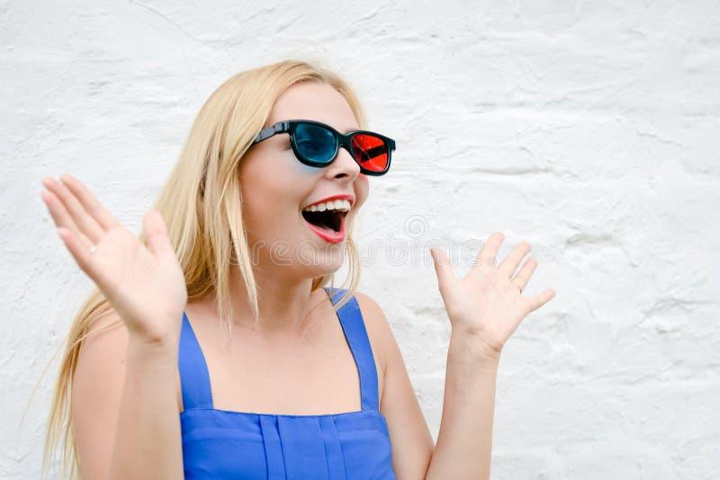 与3D玻璃的美好的少妇观看的电影,激发握手 免版税库存图片