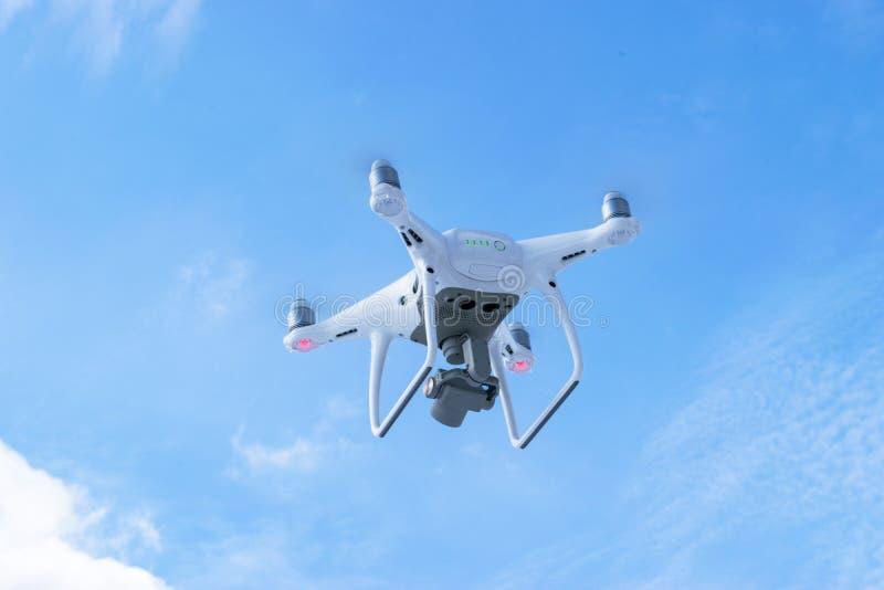 与4K摄象机的新航空器DJI幽灵4赞成quadcopter寄生虫和在天空的无线遥远的控制器飞行 通风 免版税图库摄影