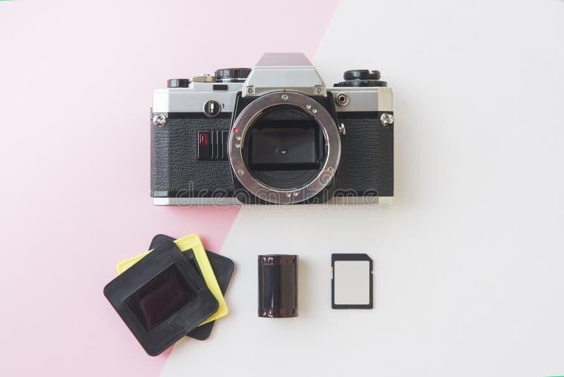 与35 mm底片、幻灯片和存储卡的SLR照相机在桃红色后面 库存照片