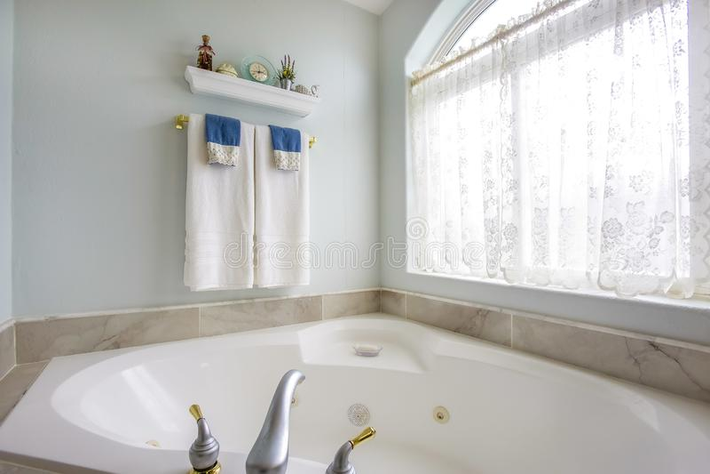 与agleaming的浴缸的卫生间内部在一个大被成拱形的窗口旁边 库存图片
