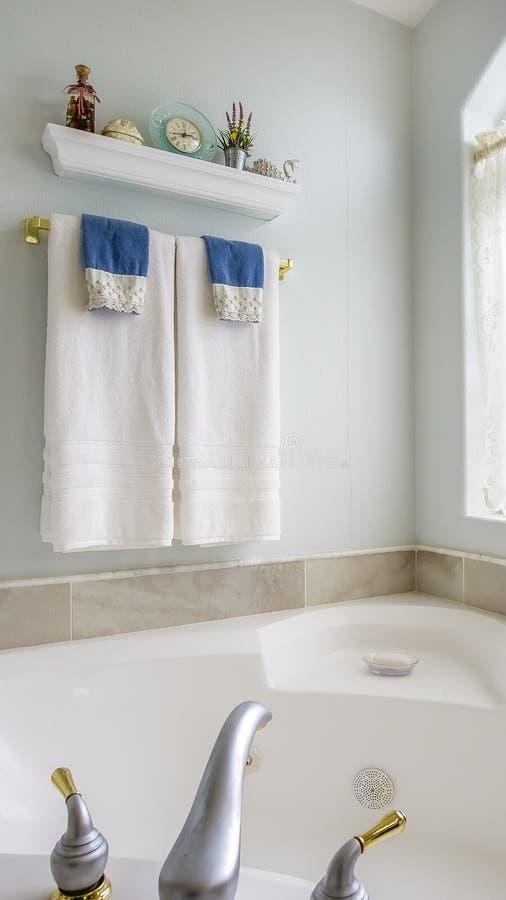 与agleaming的浴缸的垂直的卫生间内部在一个大被成拱形的窗口旁边 库存照片