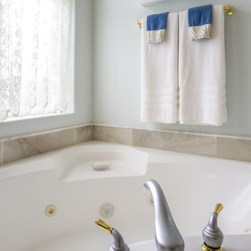 与agleaming的浴缸的方形的框架卫生间内部在一个大被成拱形的窗口旁边 免版税图库摄影