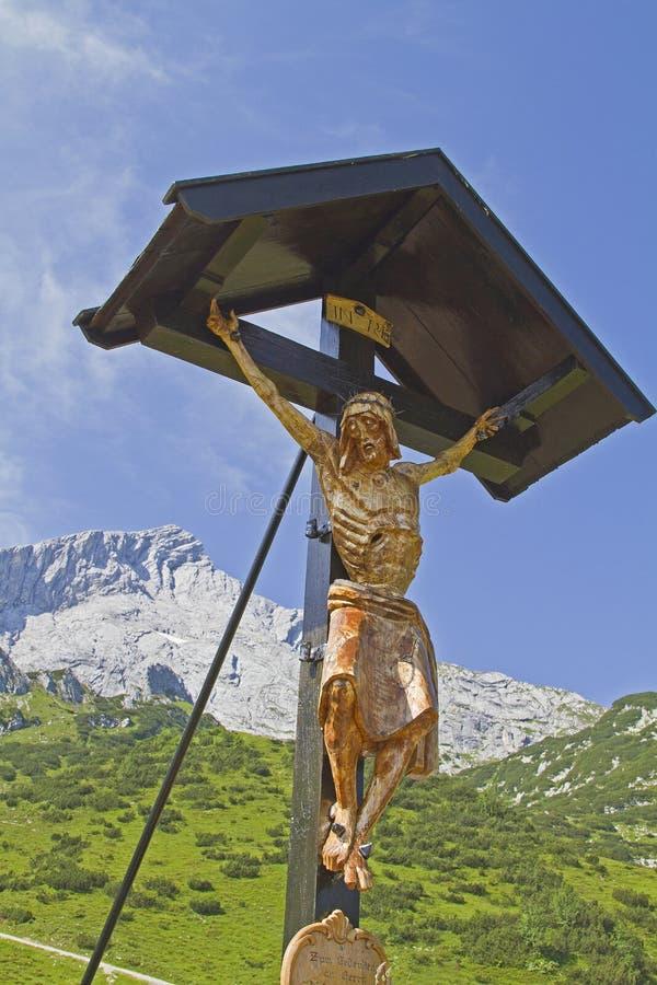 与Alpspitz山顶的木交叉 免版税库存图片