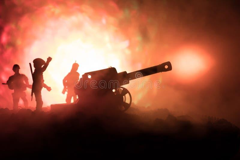 与arillery和常设战士的战斗场面 站立在领域的老野战炮剪影准备好射击 以五颜六色的黑暗 库存照片