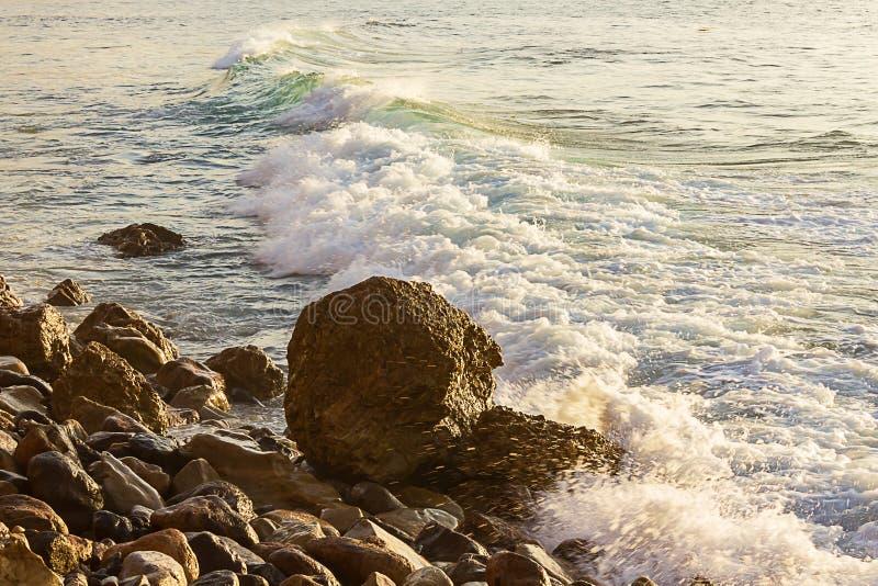 与backsplash的起泡沫的反对冰砾的碎波和泡沫在与减少入海洋的波浪的岩石岸 库存图片