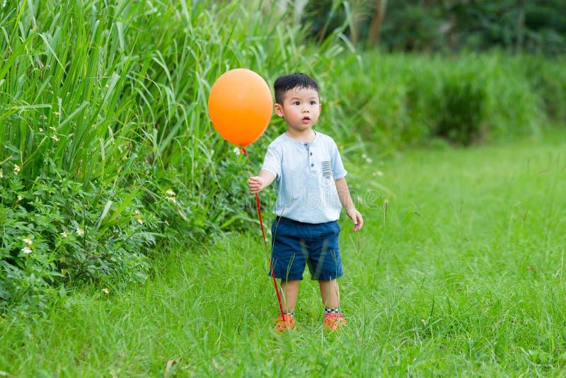 与ballooon的亚洲小男孩抓住 库存图片