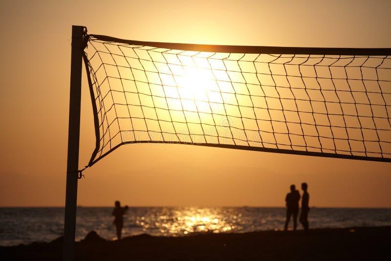 与beachball网剪影的海滩日落  库存图片