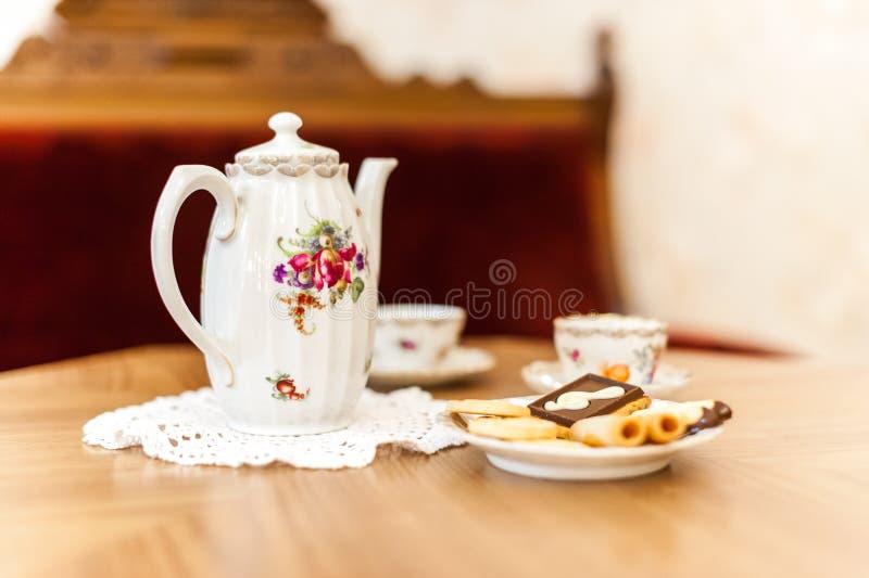 与bisquits的茶具在木桌上 免版税库存照片