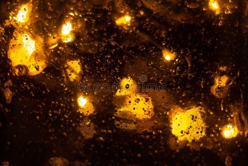 与bokeh光的金黄发光的背景 黄色闪烁的被弄脏的纹理 光和泡影抽象defocused背景 库存照片