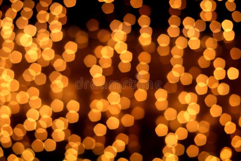 与bokeh defocused光的金黄抽象背景 免版税库存照片