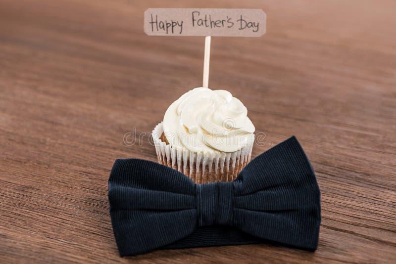 与bowtie和愉快的父亲节题字的鲜美杯形蛋糕 免版税图库摄影