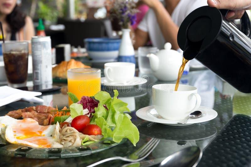 与breskfat集合的即侍者倾吐的咖啡在油煎的桌上 库存照片