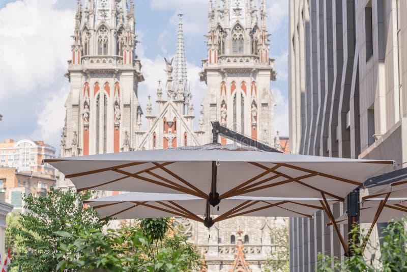 与cafe& x27的现代大厦; 在一个大阳台的s大伞与在背景的古老中世纪天主教会门面 库存图片