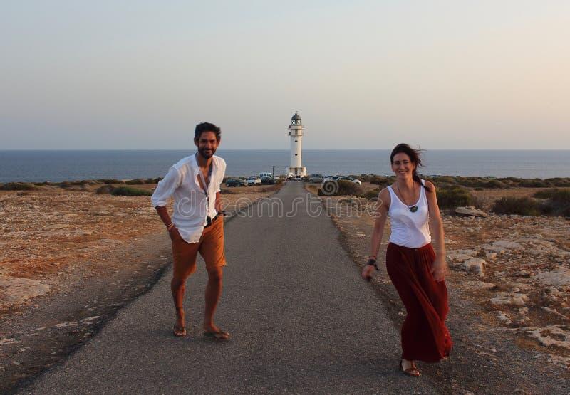 与Cap de Barberia ` s灯塔的年轻美丽的夫妇` s画象在软的背景,福门特拉岛,巴利阿里群岛,西班牙 免版税库存照片