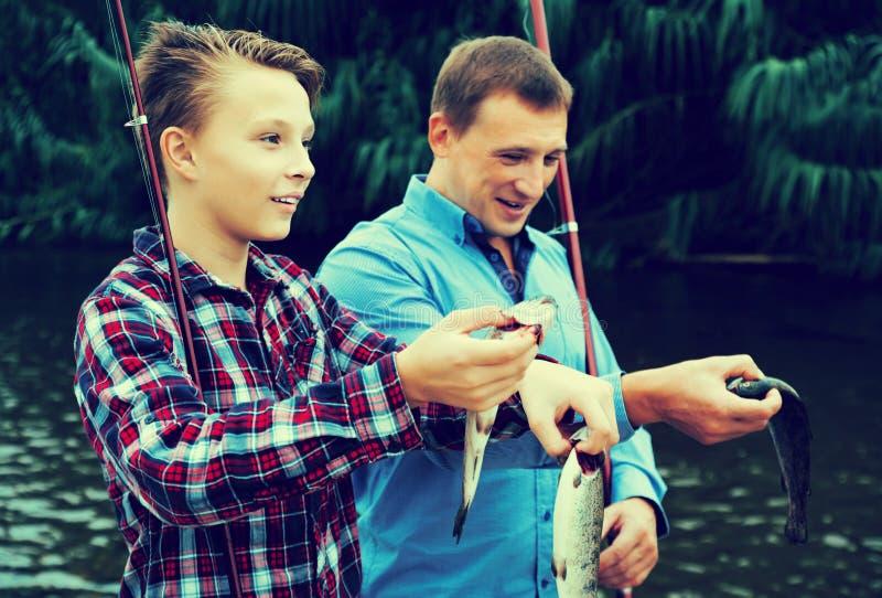 与catched鱼的家庭 免版税库存照片