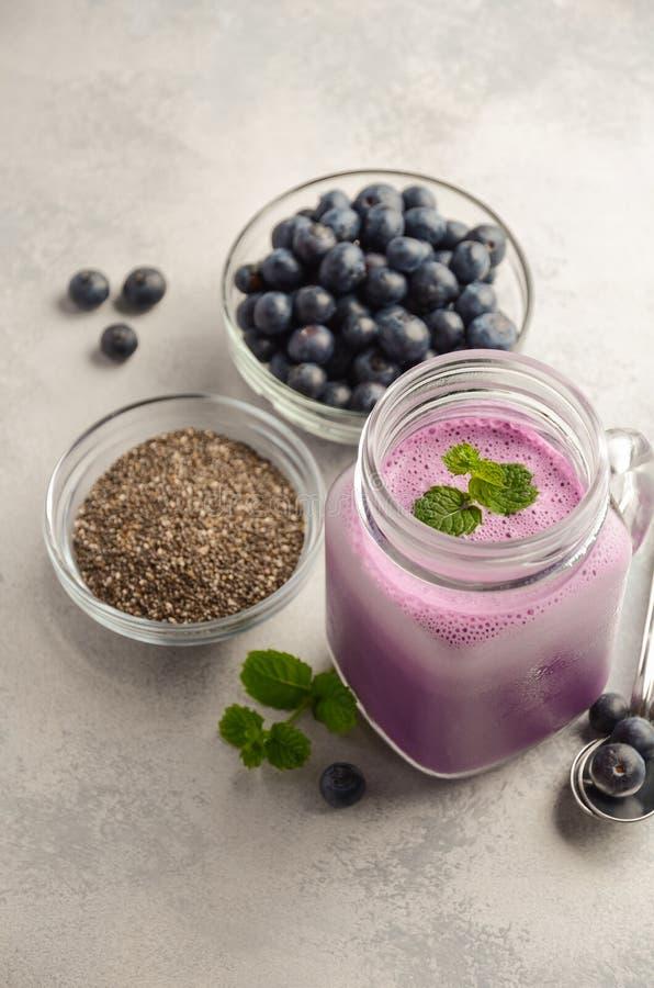 与chia种子的蓝莓圆滑的人在灰色具体背景的玻璃瓶子 免版税库存图片