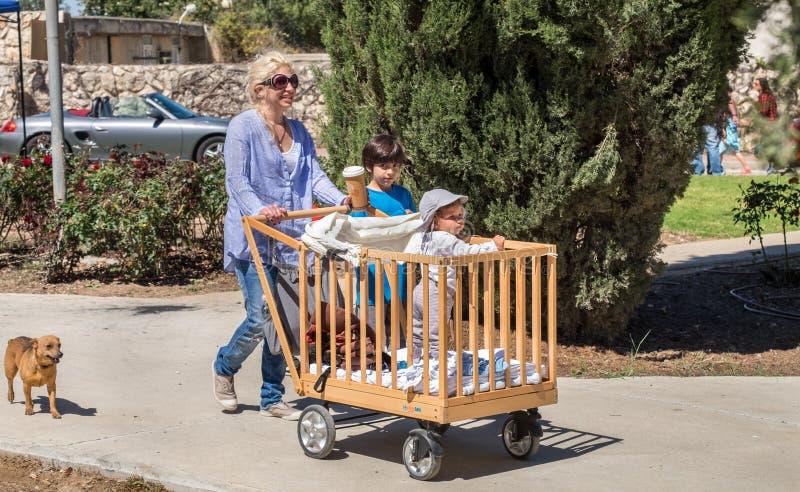 与childs的妈妈步行在古板的木婴儿车 库存图片