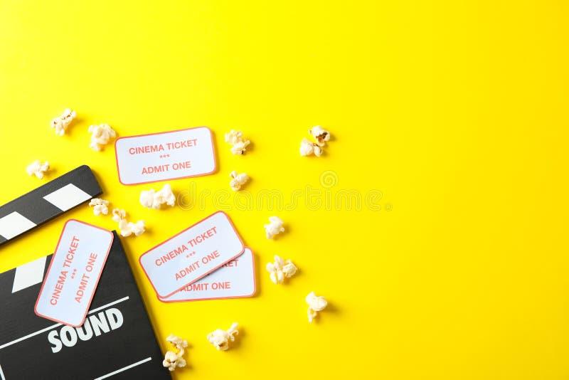 与clapperboard、玉米花和票的平的被放置的构成 免版税库存图片